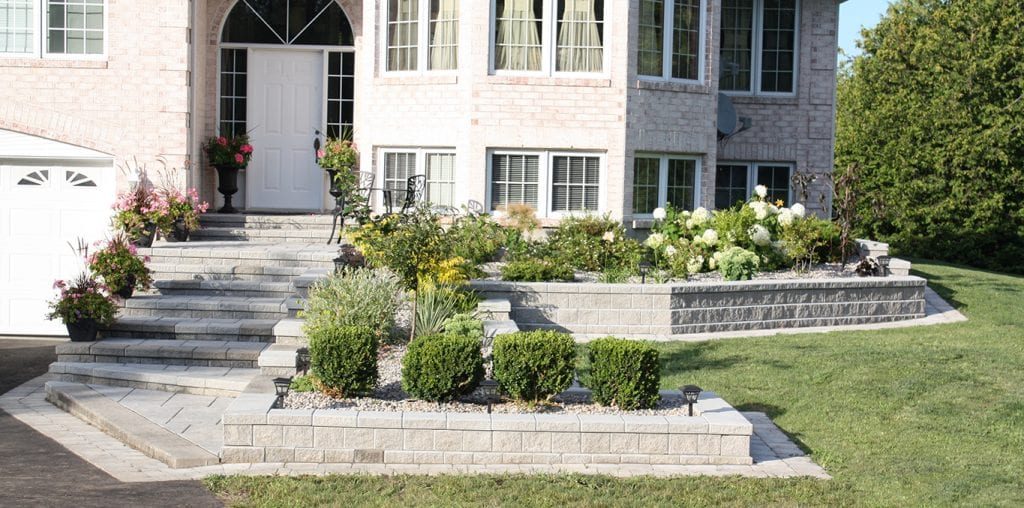 Steps leading to a house with a multi-tiered garden beside the stairway