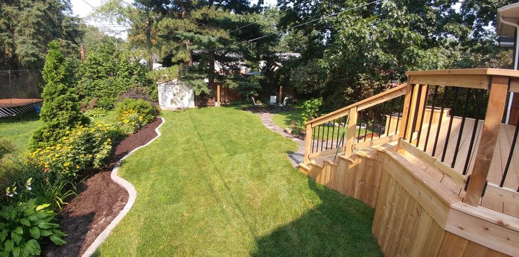 A recently landscaped backyard with wood patio