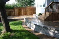 Raised stonework patio with wooden stairway leading to house