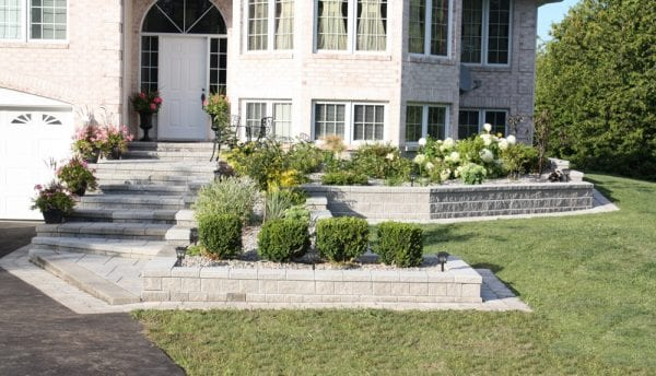 Elegant entrance stairway leading to a large home, with a tiered garden bordering the stairway
