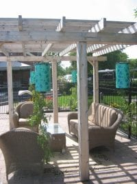 Aged cedar pergola on a patio with outdoor furniture